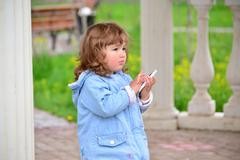 Girl two years, with a cell phone in the park - stock photo