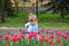Little girl near the flower beds with tulips - stock photo