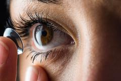 Woman about to insert her contact lens Stock Photos