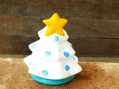 christmas tree with yellow star ceramic on wooden background still life - stock photo