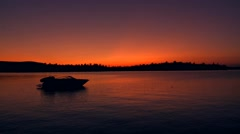 Speed boat anchored in a lake at sunset. Stock Footage