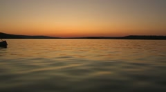 Two people canoeing on a lake at sunset. Stock Footage