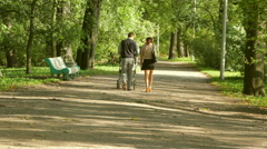Young couple with baby carriage in Park Stock Footage