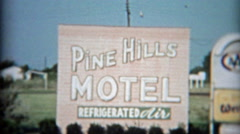 Stock Video Footage of 1957: Pine Hills Motel enterance sign and motor lodge with old cars.