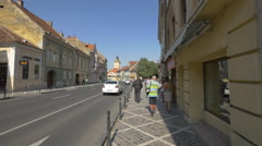 People and cars on Muresenilor street, Brasov Stock Footage