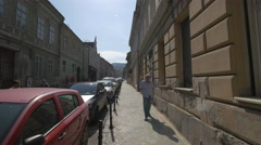 Old man walking on Poarta Schei street, near old buildings and cars, Brasov Stock Footage