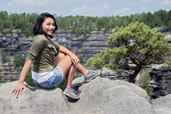 Woman sitting on a rock lookout - stock photo