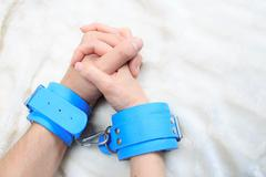 Male and female hands in handcuffs. sexy couple in bed. sex Toys - stock photo