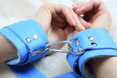 Female hands in blue leather handcuffs. eagerly grabbed the sheets.. sex toys Stock Photos
