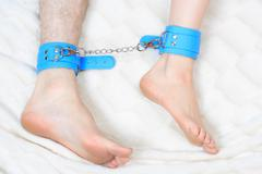 male and female legs in handcuffs. couple in bed. sex Toys - stock photo