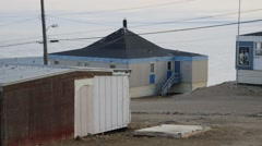 People passing by buildings on the roads of Pond Inlet. (Pan) Stock Footage