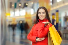 Happy Girl in a Red Coat Shopping in a Mall - stock photo