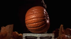 Slow motion shot of a pumpkin being smashed by a kettle bell. - stock footage