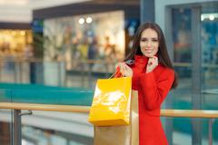 Happy Girl in a Red Coat Shopping in a Mall Stock Photos