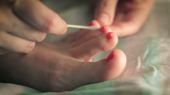 Woman paints her toenails red lacquer Stock Footage