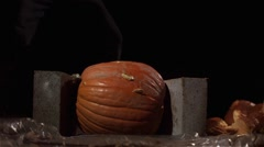 Slow motion shot of a pumpkin being smashed by a baseball bat. - stock footage