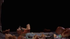 Slow motion shot of a semi broken pumpkin being smashed on a cinder block. - stock footage