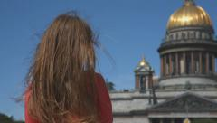 Girl looks at St. Isaac's Cathedral, old Russian temple Stock Footage