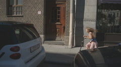 Girl riding a scooter on the street - stock footage