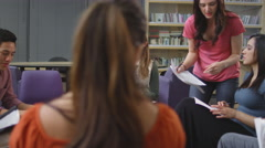 A student asks her classmates for help in a study session Stock Footage