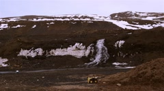 Mountain runoff waterfall in  Arctic Bay, Nunavut pan to town. (Pan Left) Stock Footage