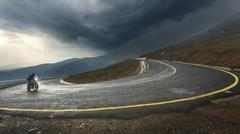 Driving a motorcycle on alpine highway toward the storm Stock Photos