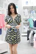 Lovely young pregnant woman looking for baby clothes in a store. Stock Photos