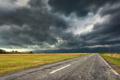 Driving on an empty old road at stormy weather Stock Photos