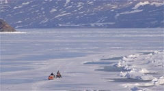 A snowmobile towing a qamutik across sea-ice in Arctic Bay, Nunavut. - stock footage