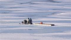 Snowmobile towing a qamutik across sea-ice in Arctic Bay, Nunavut. - stock footage