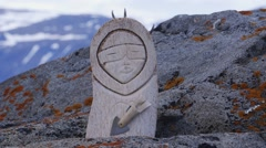 Carving of a traditionally dressed inuit displayed outside on a rock ledge. Stock Footage