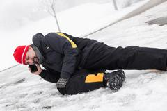Stock Photo of Casualty man is lying on a icy way and calling the ambulance