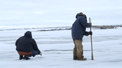 Pair of fisherman cut holes in sea ice during an Arctic expedition. Stock Footage