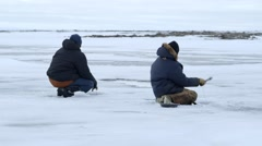 Pair of fisherman ice-fishing during an arctic expedition. - stock footage