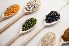 Wooden spoons of pulses and seeds Stock Photos