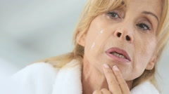 Senior woman applying cosmetic lotion on her face - stock footage