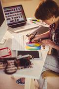 Casual female designer working with digitizer and colour chart Stock Photos