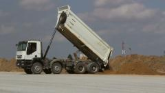 Stock Video Footage of Dumper truck unloading soil at construction site during road works