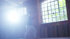 4K Asian martial artist training alone, practising moves in industrial building Stock Footage