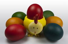 Group of Easter Eggs with Chick Egg holder carrying Red Egg - stock photo