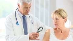 Elderly woman consulting doctor for skin control Stock Footage