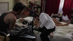 Shooting the erotic scenes of the film. The guy kisses the girl on the bed - stock footage