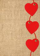 Border frame of red hearts on sack canvas burlap background texture - stock photo
