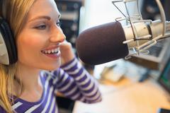 Stock Photo of Happy young female radio host broadcasting in studio