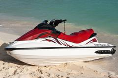 Jet ski on beach sand near sea Stock Photos