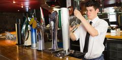 Stock Photo of Barkeeper holding glass in front of beer dispenser