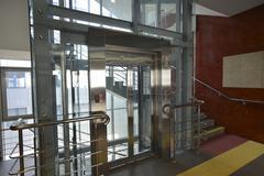 Hall with atransparent glass elevator - stock photo