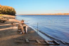 Fisherman at the river - stock photo