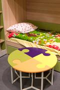 Fragment  interior children's room with a table in  form of  puzzle - stock photo