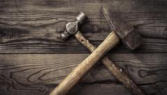 Old retro hammers on wooden workbench - stock photo